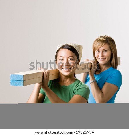 Happy friends carrying lumber - stock photo