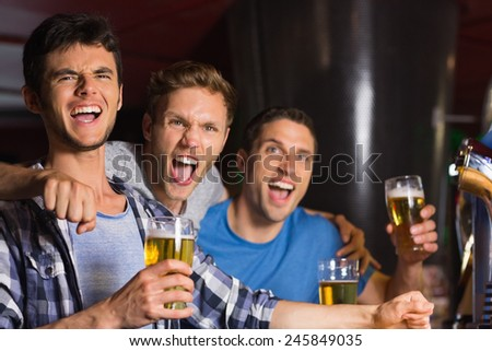 Happy friends catching up over pints in a bar - stock photo