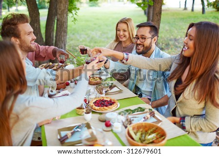 Happy friends cheering up at Thanksgiving party outdoors - stock photo