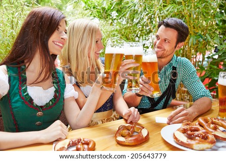 Happy friends clinking beer glasses in summer in bavaria - stock photo