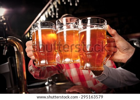 Happy friends clinking with beer mugs in pub,  - stock photo