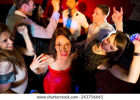 Happy friends dancing and smiling at the nightclub - stock photo