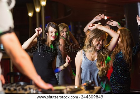 Happy friends dancing by the dj booth at the nightclub - stock photo