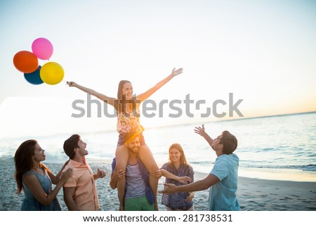 Happy friends dancing on the sand with balloon at the beach - stock photo
