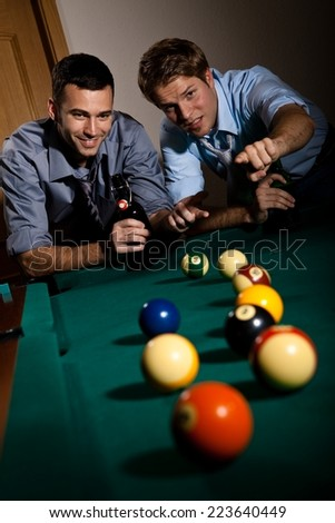 Happy friends discussing a game of billiard at table with beer in hand. Selective focus, pointing. Having fun. - stock photo