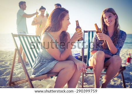 Happy friends doing barbecue and drinking beer at the beach - stock photo