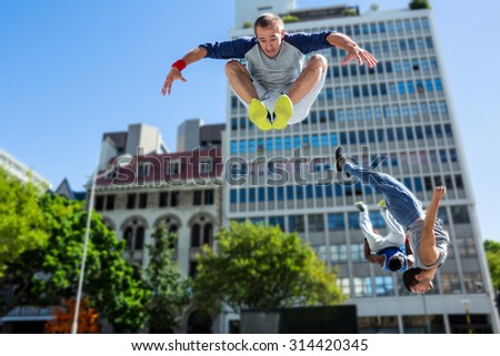Happy friends doing parkour in the city on a sunny day - stock photo