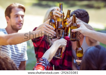 Happy friends drink beer in the park on a sunny day - stock photo