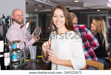 Happy friends drinking and chatting with smiling barman at bar counter - stock photo