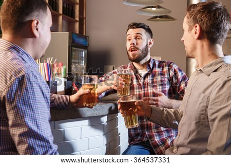 Happy friends drinking beer at counter in pub - stock photo