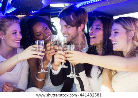 Happy friends drinking champagne in limousine - stock photo
