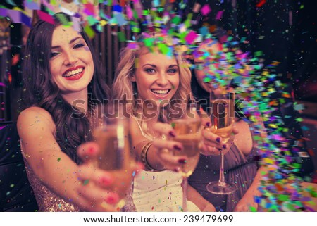 Happy friends drinking cocktails together against colour curve - stock photo