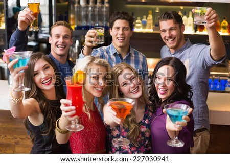 Happy friends drinking cocktails together at the bar - stock photo