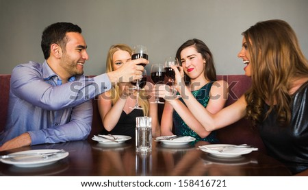 Happy friends drinking red wine in a bar and toasting each other - stock photo
