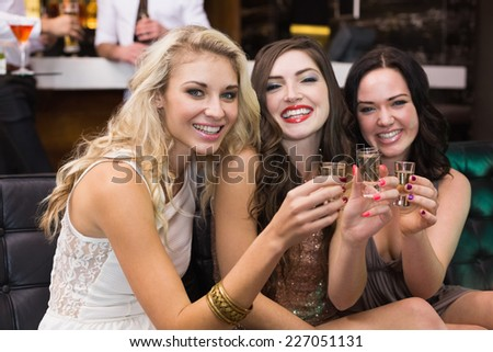 Happy friends drinking shots together at the bar - stock photo