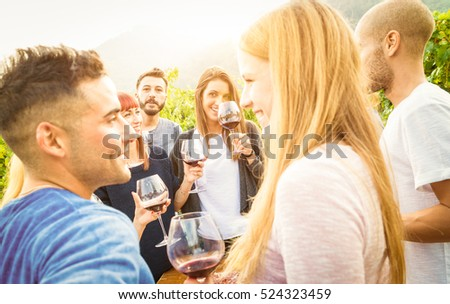 Happy friends drinking wine and having fun together - Friendship concept with young people enjoying harvest time at farmhouse vineyard countryside - Warm desat  filter with focus on background face