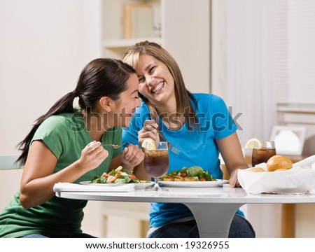 Happy friends eating healthy lunch and laughing - stock photo