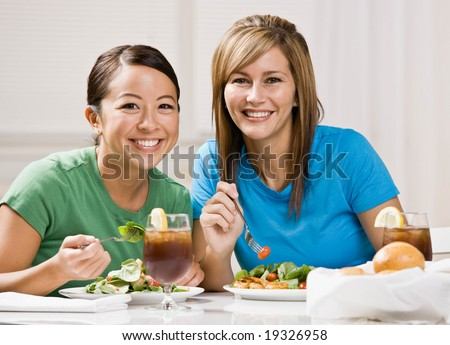 Happy friends eating healthy lunch and smiling - stock photo