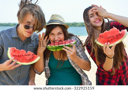 Happy friends eating watermelon on the beach. Youth lifestyle. Happiness, joy, friendship, holiday, beach, summer concept. Group of young people having fun outdoor. - stock photo