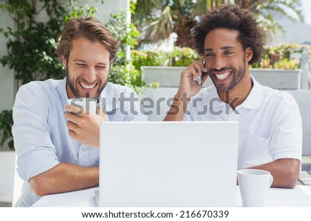 Happy friends enjoying coffee together with laptop outside at the coffee shop - stock photo
