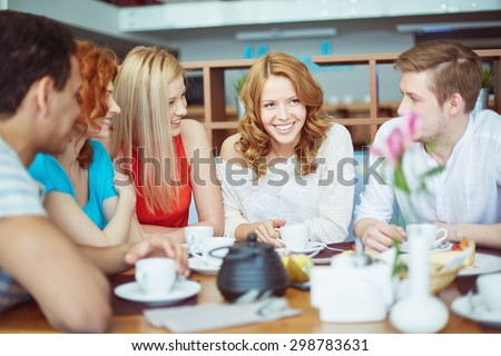 Happy friends enjoying time in cafe - stock photo