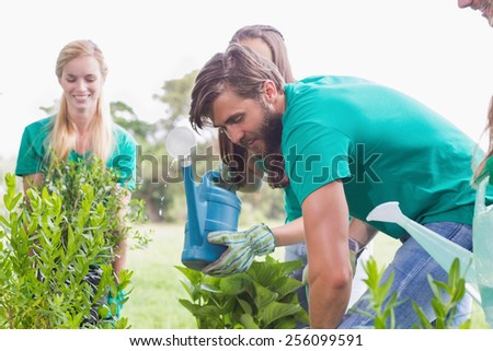 Happy friends gardening for the community on a sunny day - stock photo