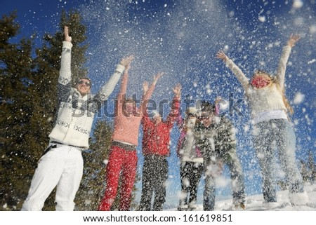 happy friends have fun at winter on fresh snow, healthy young people group outdoor