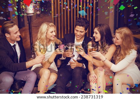 Happy friends having a drink together against flying colours - stock photo