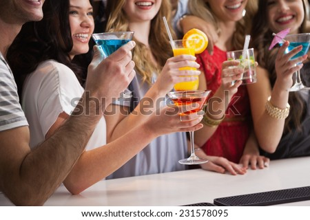 Happy friends having a drink together in a bar
