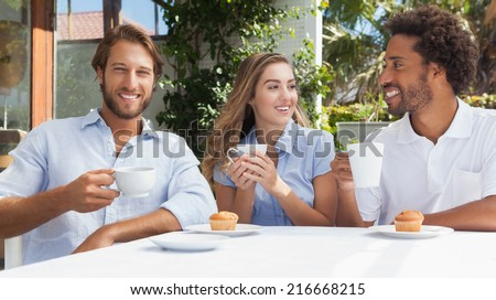 Happy friends having coffee together outside at the coffee shop - stock photo
