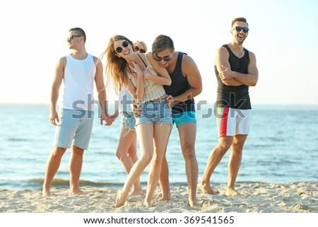 Happy friends having fun at the beach, outdoors - stock photo