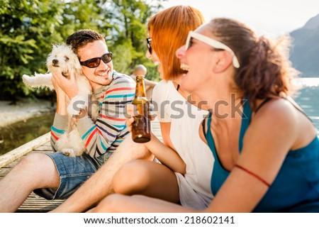 Happy friends having fun at the lake - stock photo