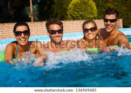 Happy friends having fun in outdoor swimming pool at summertime, laughing.