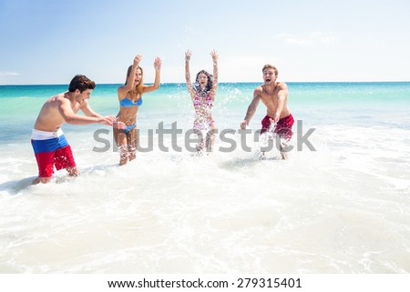 Happy friends having fun in the water together at the beach - stock photo