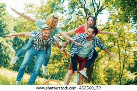 Happy friends having fun together on a summers day.Young cheerful people piggybacking in the park during springtime. - stock photo