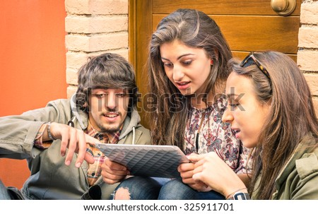 Happy friends having fun with modern digital tablet - Young students studying together outdoors with electronic device - University free time concept with high school people - Main focus on the guy