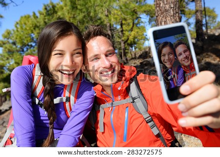 Happy friends hikers taking selfie on hiking trip. Couple posing for self-portrait picture on smartphone during summer holidays vacation travel camping and backpacking. Young multiracial couple. - stock photo