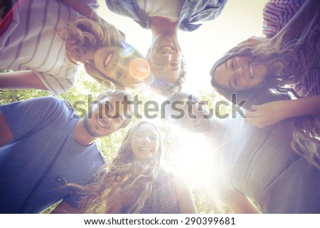 Happy friends huddling in circle in the park on a sunny day - stock photo