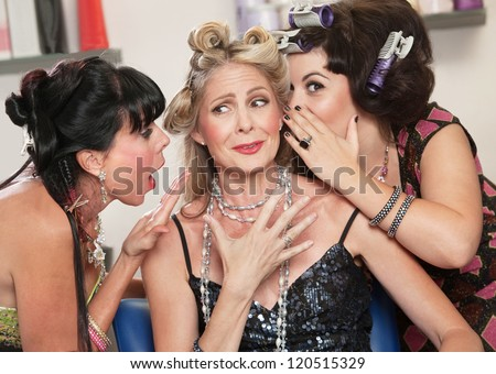 Happy friends in hair salon whispering to each other - stock photo