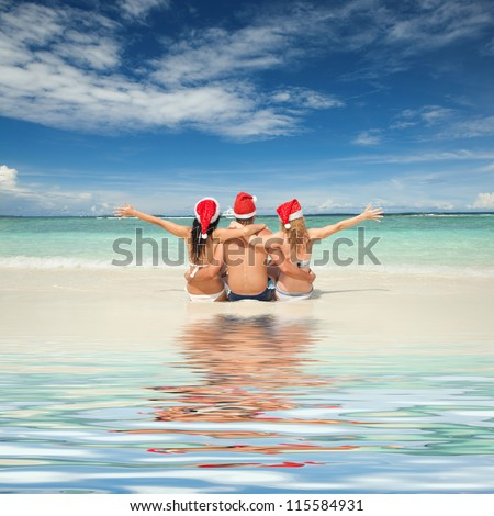 Happy friends in santa hats on the beach. Christmas vacation - stock photo