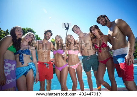 Happy friends in swimwear standing together with arms around