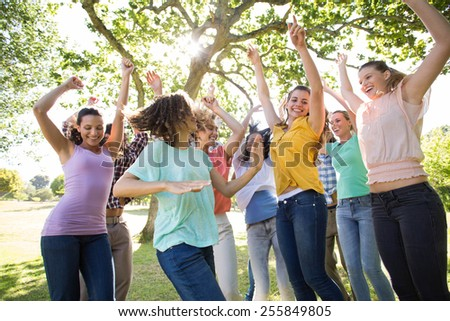 Happy friends in the park cheering on a sunny day - stock photo