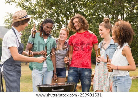 Happy friends in the park having barbecue on a sunny day - stock photo