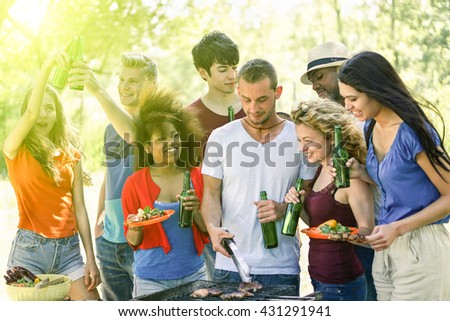 Happy friends in the park having barbecue on a sunny day - Group of multi ethnic people eating and drinking outdoor - Concept about good and positive mood with friends - Vintage editing - stock photo