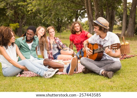Happy friends in the park having picnic on a sunny day - stock photo