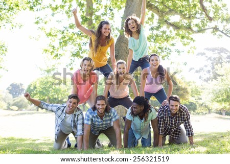 Happy friends in the park making human pyramid on a sunny day - stock photo
