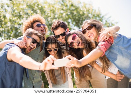 Happy friends in the park taking selfie on a sunny day - stock photo