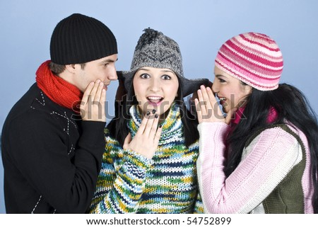 Happy friends  in winter season having fun,a young woman standing in middle and looked surprised  while her friends telling her a secret and raise the cap ears over blue background - stock photo