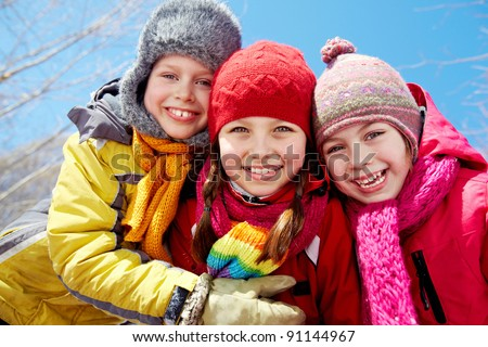 Happy friends in winterwear looking at camera outside - stock photo