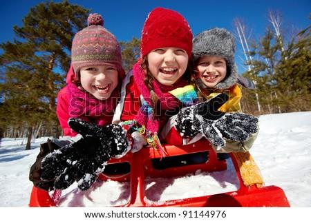 Happy friends in winterwear spending time in park - stock photo